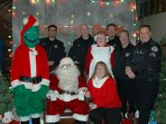 Photo of SHPD staff with Santa, Ms. Claus, and The Grinch at the 2015 Donut Day event